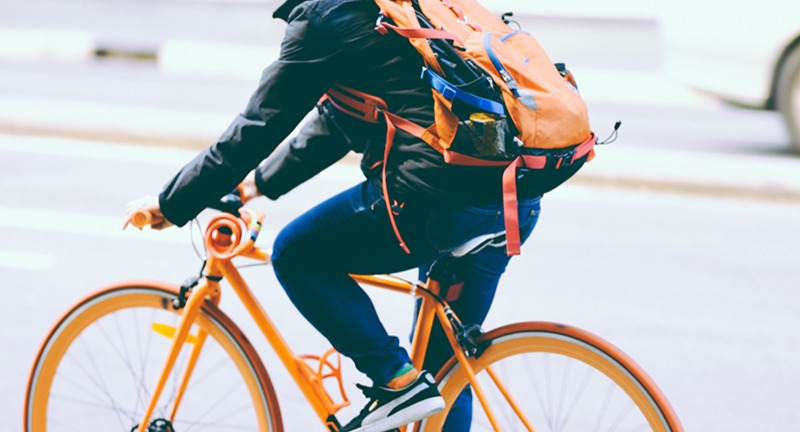 Person riding orange commuter bike