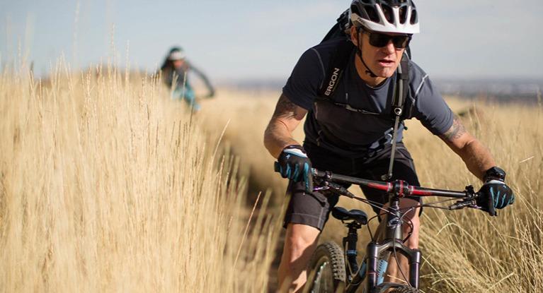 Man riding bike wearing hydration pack