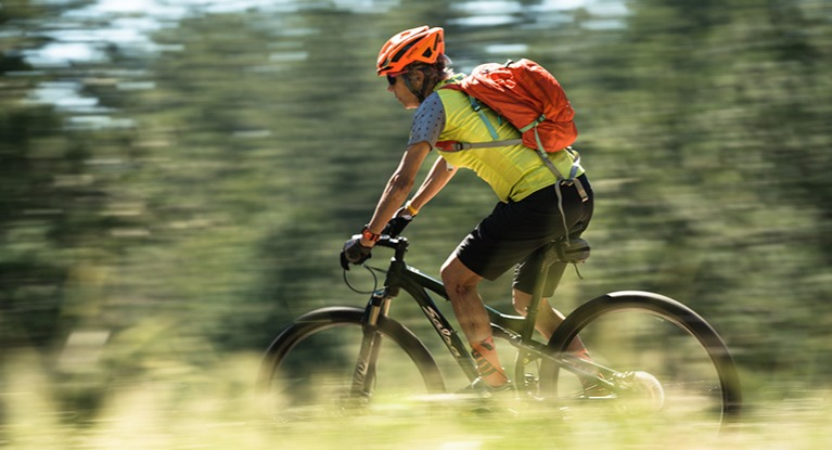 Woman on mountain bike with backpack