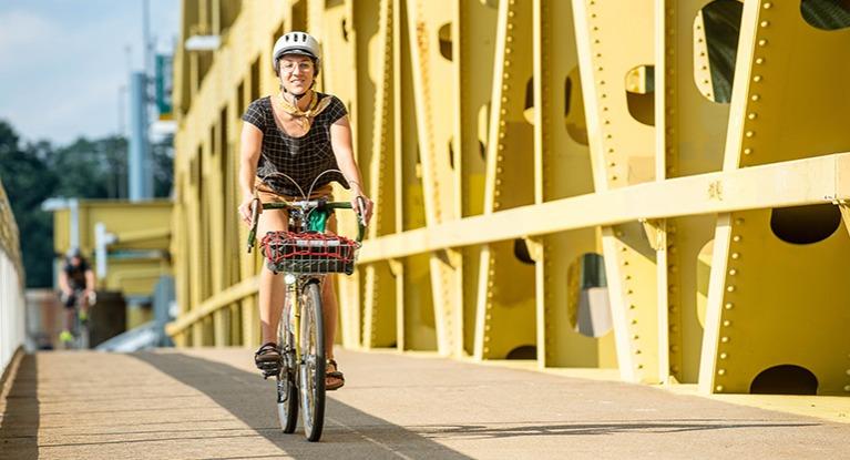 Woman riding a bike across a bridge.