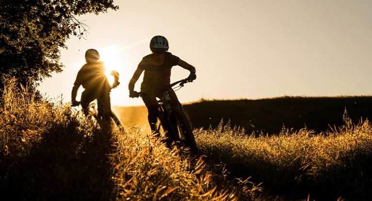 pair of cyclists at sunset