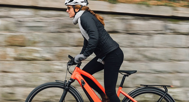 Woman riding an orange electric bike