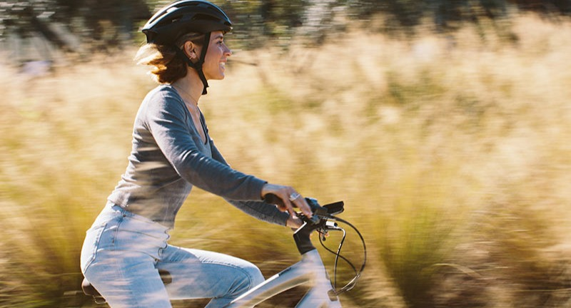 A woman riding an eBike on a path.