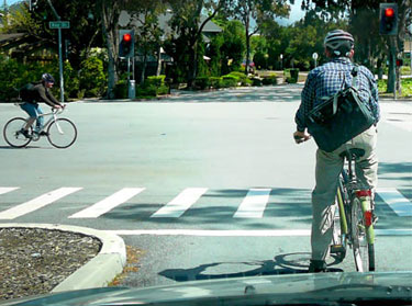 At the red light, this cyclist has moved to the center of the road in order to trip the detector beneath the pavement there.