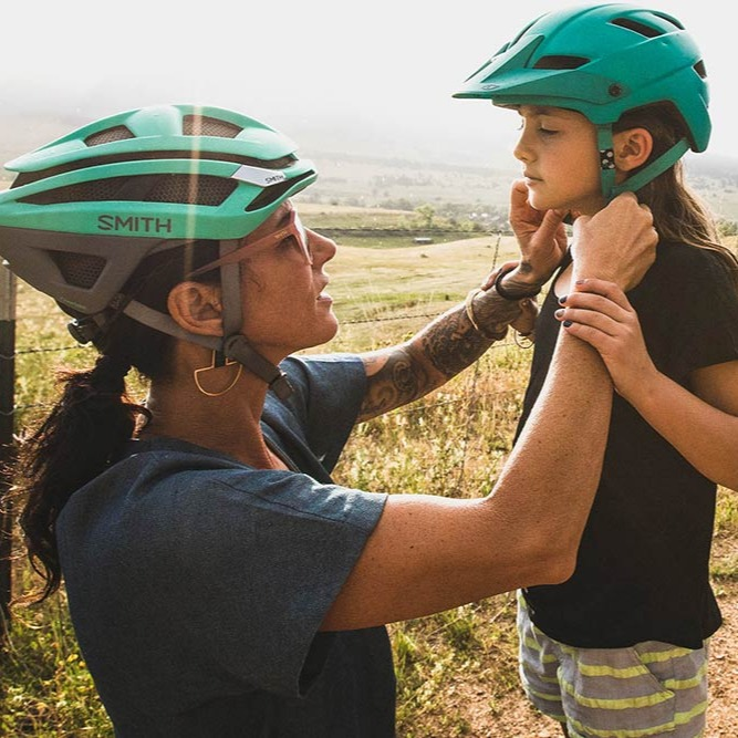 Two people putting on helmets