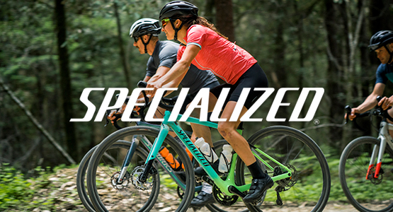 Man and woman riding Specialized Diverge bikes in woods