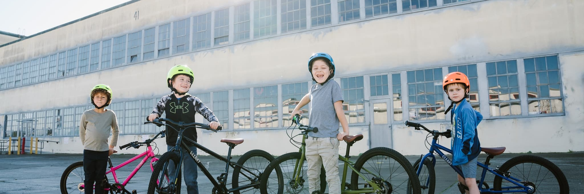 Four kids standing with their kids bikes in a warehouse area
