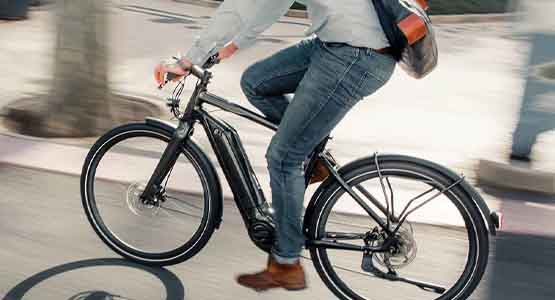A man with jeans riding a Giant electric bike with a messenger bag