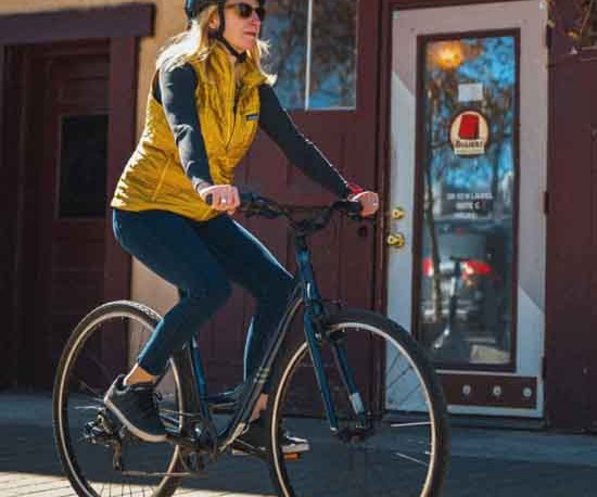 A woman riding a blue batch Step Thru Comfort bike in town