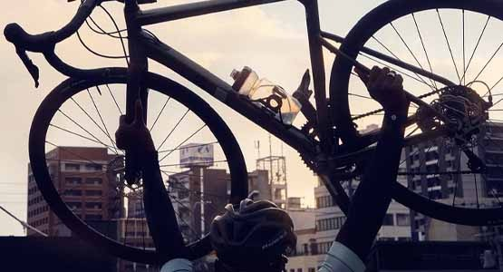 A man lifting a Cannondale CAAD13 bike in the air in the city