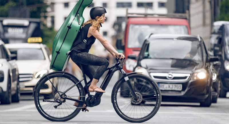 A woman with a guitar riding a black Cannondale electric bike in the city
