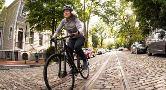 A woman riding a Cannondale Quick Bike on a brick paved street