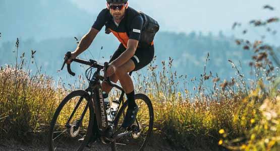 A man riding a Cannondale Synapse bike on a trail