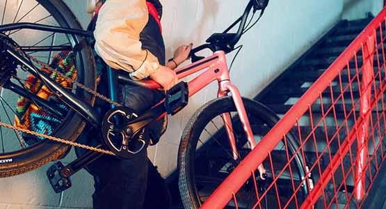 Person carrying a Cannondale Treadwell bike up a stairwell on their shoulder