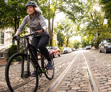 Woman riding a Cannondale bike on cobblestone street