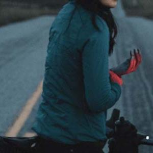 A woman on a bike wearing a Specialized long sleeve bike jersey