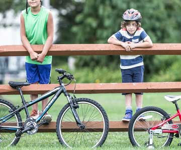 Two kids looking at their bikes on a fence