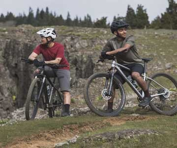 2 riders with helmets riding Specialized Rockhopper bikes on a trail