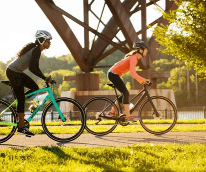 2 Women riding Specialized Sirrus bike on bike trail