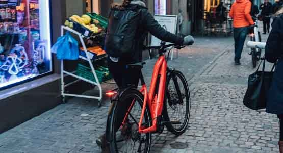 Woman wearing jacket and backpack walking an orange Specialized electric bike
