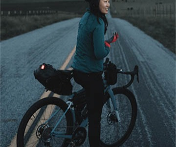 Woman on Specialized Road Bike with Gloves, Bags and Lights