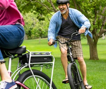 A man riding an Electra Townie electric bike in a park riding behind another rider