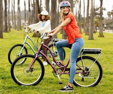 2 women on Electra Townie electric bikes in a park with helmets