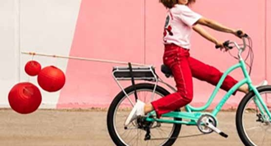 A woman with red pants riding a green Electra bike towing red balloons