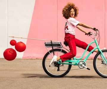 A woman riding a Electra Townie electric green bike with red balloons trailing behind her