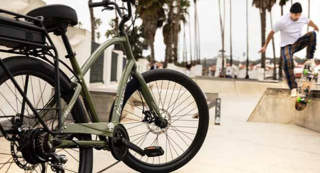 A green Electra Townie Go electric bike parked with a skater in the background