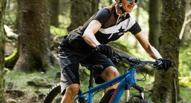 Woman Riding a Blue Cannondale Mountain Bike in Forest
