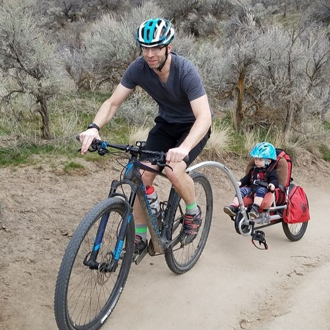 Josh on a bike with a kiddo trailer.
