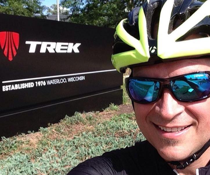 Steve in cycling gear by the Trek sign in Waterloo WI