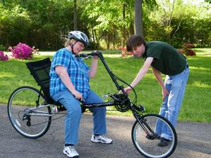 Employee showing recumbent rider some bike features