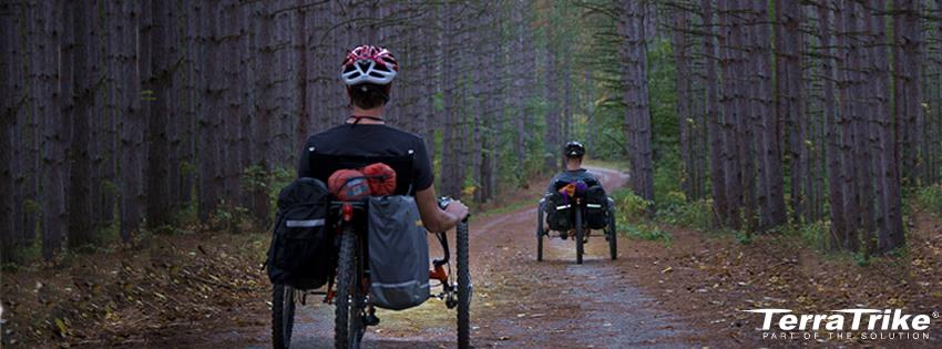 Picture of folks riding TerraTrike recumbent Trikes on a forested path