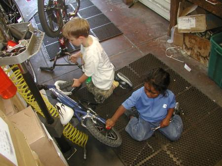 Two children working on bikes