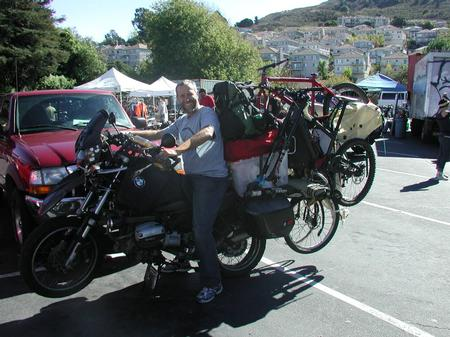 Person sitting on a motorcycle with a bike rack.