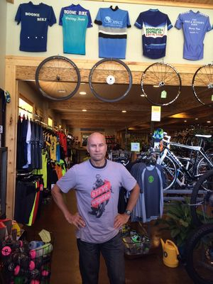 Dean Lyons below his collection of original Boone Bike jerseys on display at the new shop.