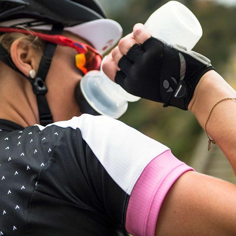 woman cyclist wearing road bike jersey and helmet drinking water