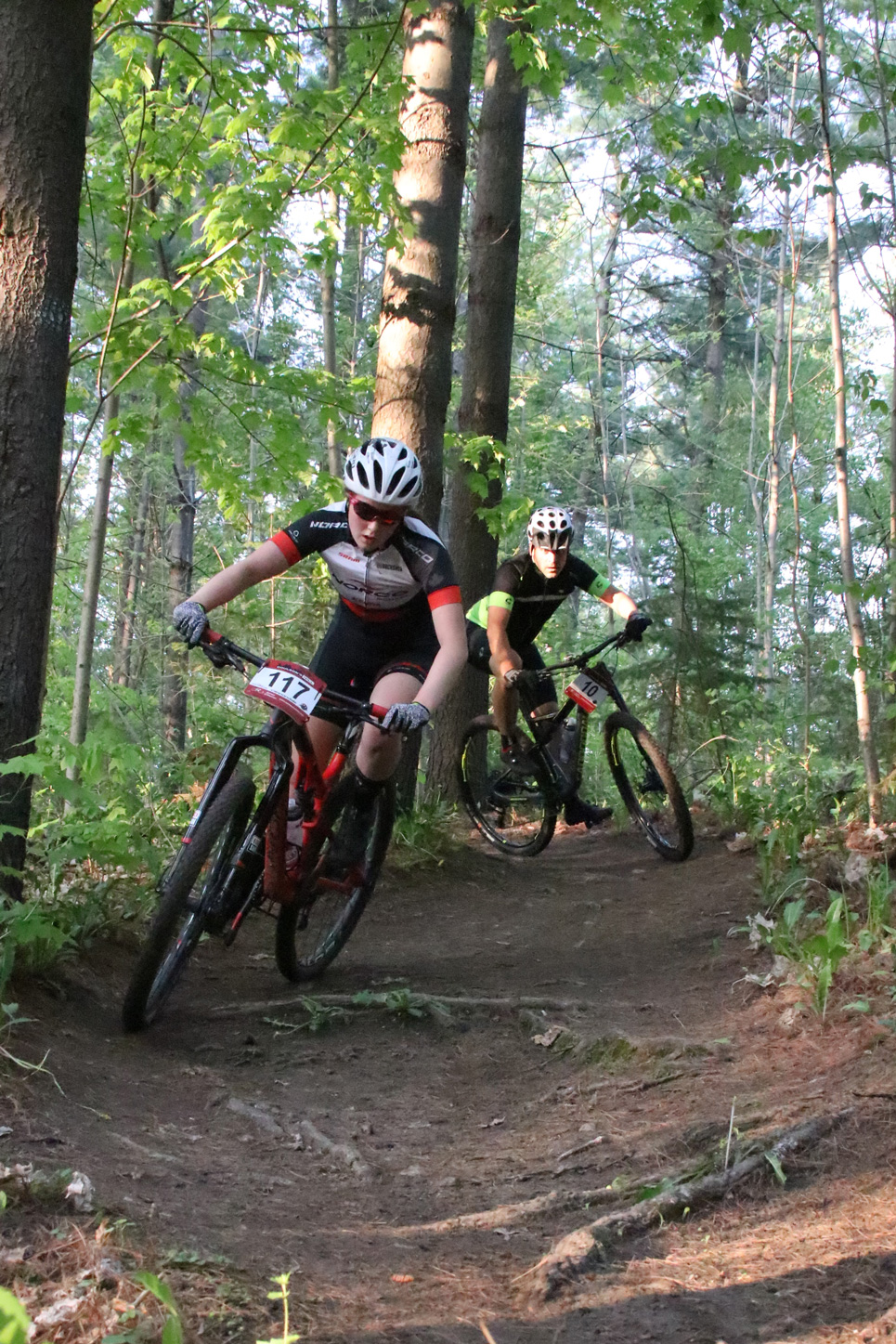 Carys Reid and Paul Boken rip through some immaculately groomed singletrack. Pursuing.