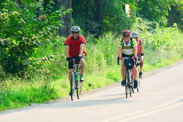 Three road cyclists ride together on a paved country road