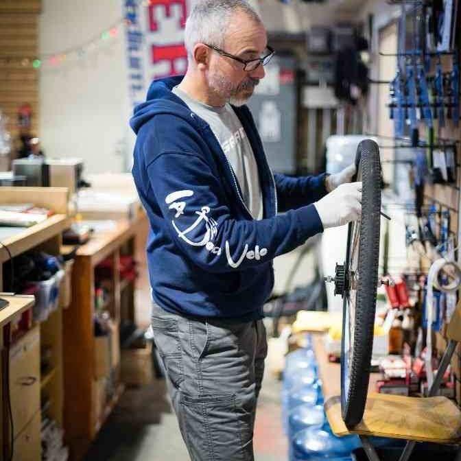 Man repairs flat in shop.