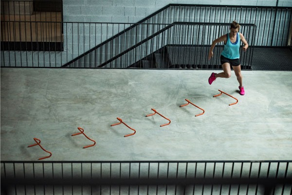 woman jumping over hurdles indoors
