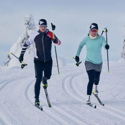 two xc skiers skiing classic style in machined track