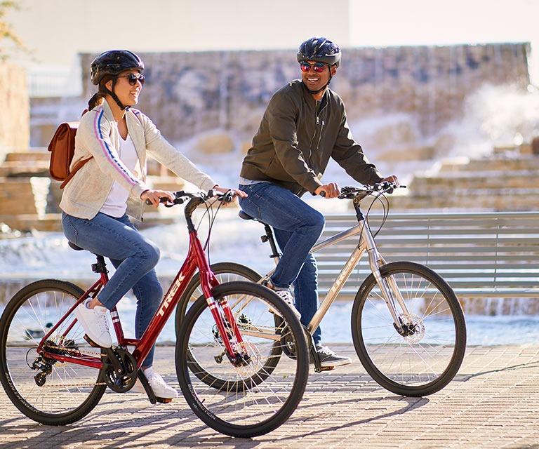 Two people riding hybrid bikes
