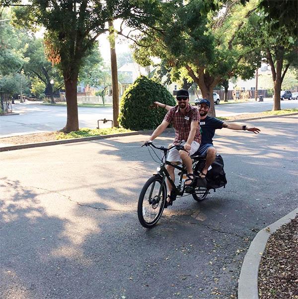 Two people riding on a cargo bike