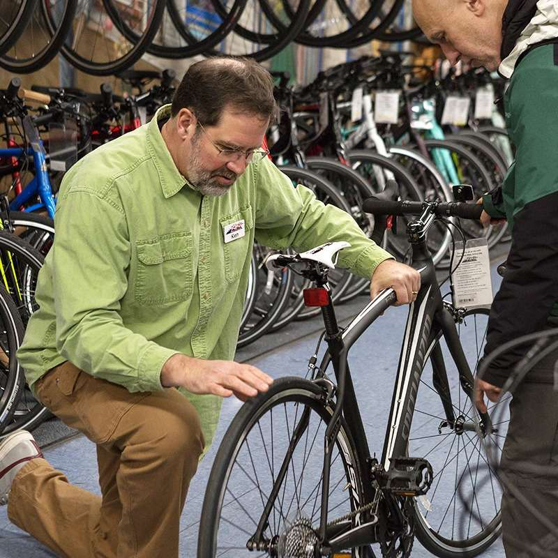 Sales Associate pointing out tires on a bike