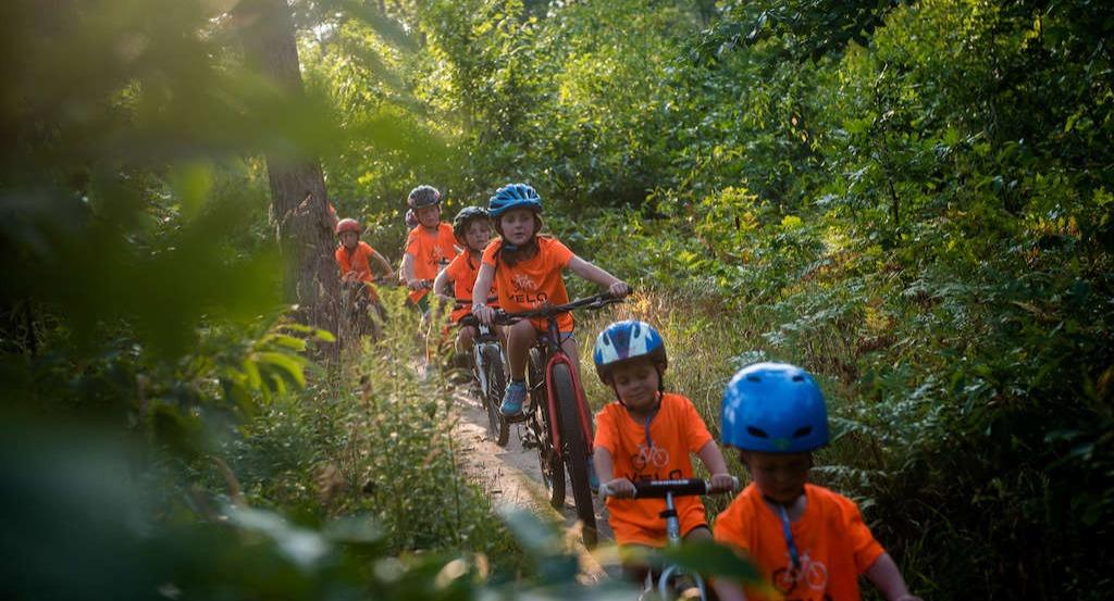 group of Velo Kids riding singletrack