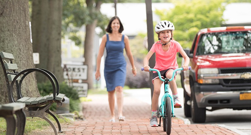 girl learning to ride bike with mother