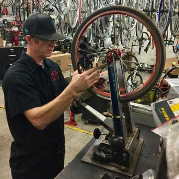 Bike maintenance and bike repair - Jerry truing a wheel at Action Sports